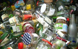 Nærbilde av en haug med syltetøyglass med metall-lokk og glassflasker. Dette sorteres i kategorien glass.