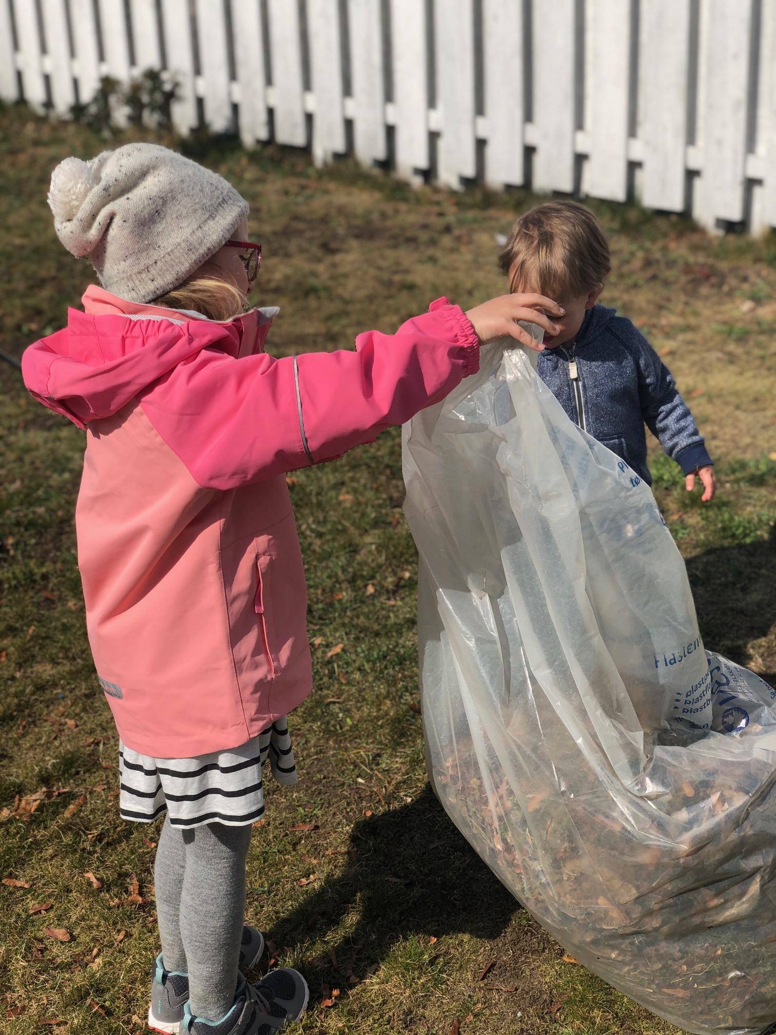 Jente og gutt som holder klar søppelsekk i hage