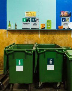 Avfallsbeholdere med nye merker og plakater på fargerik vegg